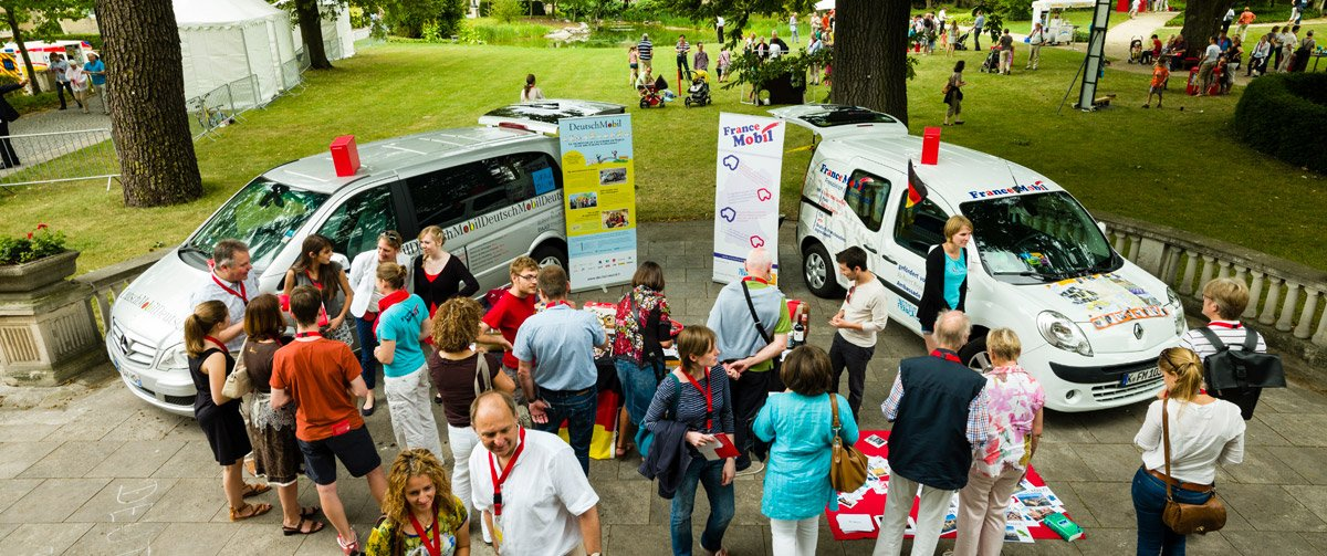 The Francemobil stands in a park and many people get informed about the opportunities.
